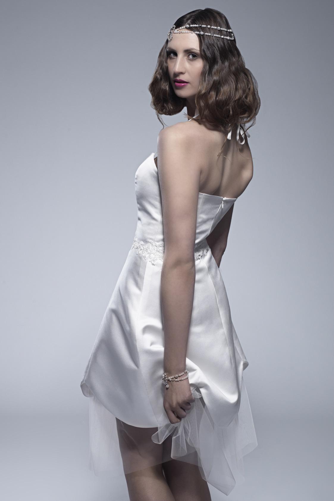 Im Bild zu sehen ist eine junge dunkelhaarige Frau mit kurzen Haaren. Sie trägt einen silbernen Kopfschmuck und ein kurzes weißes Kleid. Sie hat dem Betrachter leicht den Rücken zugedreht und schaut über die Schulter.