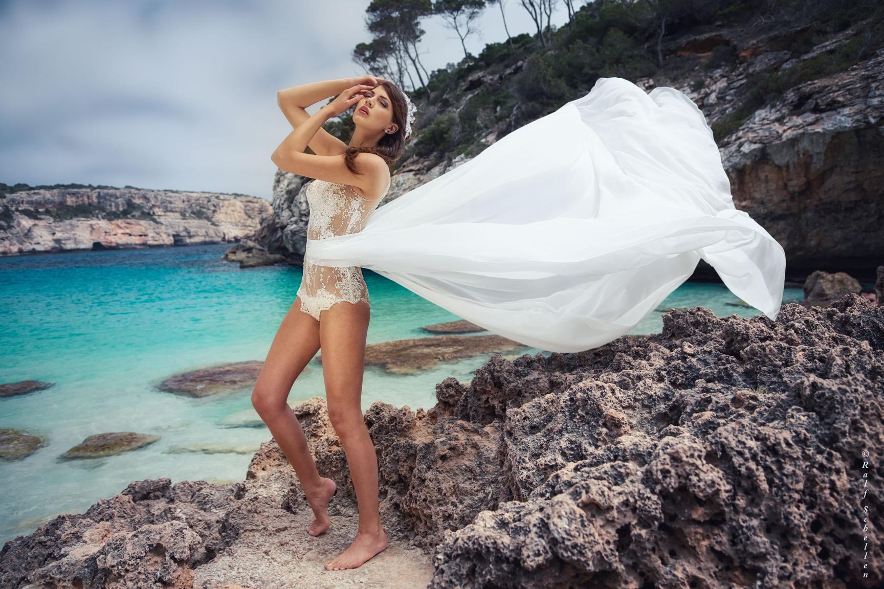 Eine junge Frau steht auf vielen Felsen vor der Kulisse des Meeres. Sie trägt einen weißen Spitzenbody mit einer Chiffonschleppe. Ihr Blick ist nach oben gerichtet und ihre beiden Arme winkelt sie ebenfalls nach oben. Den rechten Fuß hebt sie leicht an. Die Schleppe fliegt in der Luft.