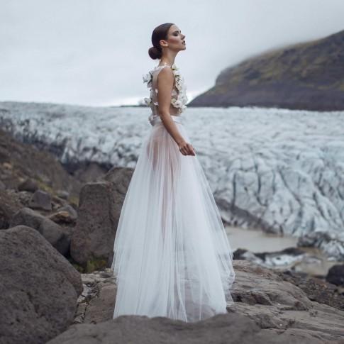 Body aus weißen Rosen Blüten und Tüll. Brautkleid Zweiteiler in Ivory vor einem Gletscher auf Island. Iceland Glacier. Hochzeitskleider handgefertigt in Düsseldorf. Designer Mode aus Deutschland.
