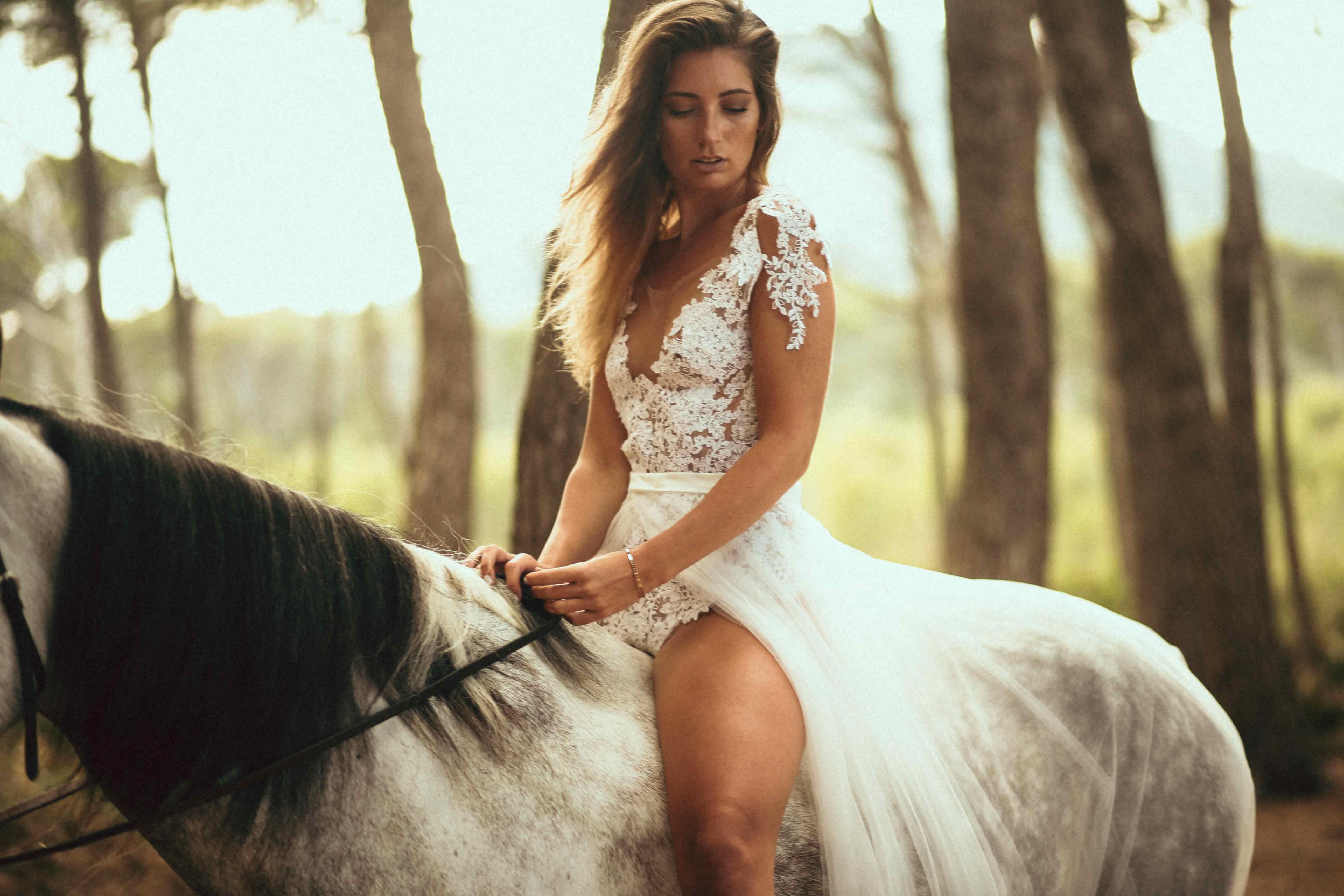 Eine blonde Frau sitzt auf dem Rücken eines Schimmels in einem spanischen Wald. Sie trägt einen Spitzenbody und eine Schleppe als Brautkleid.