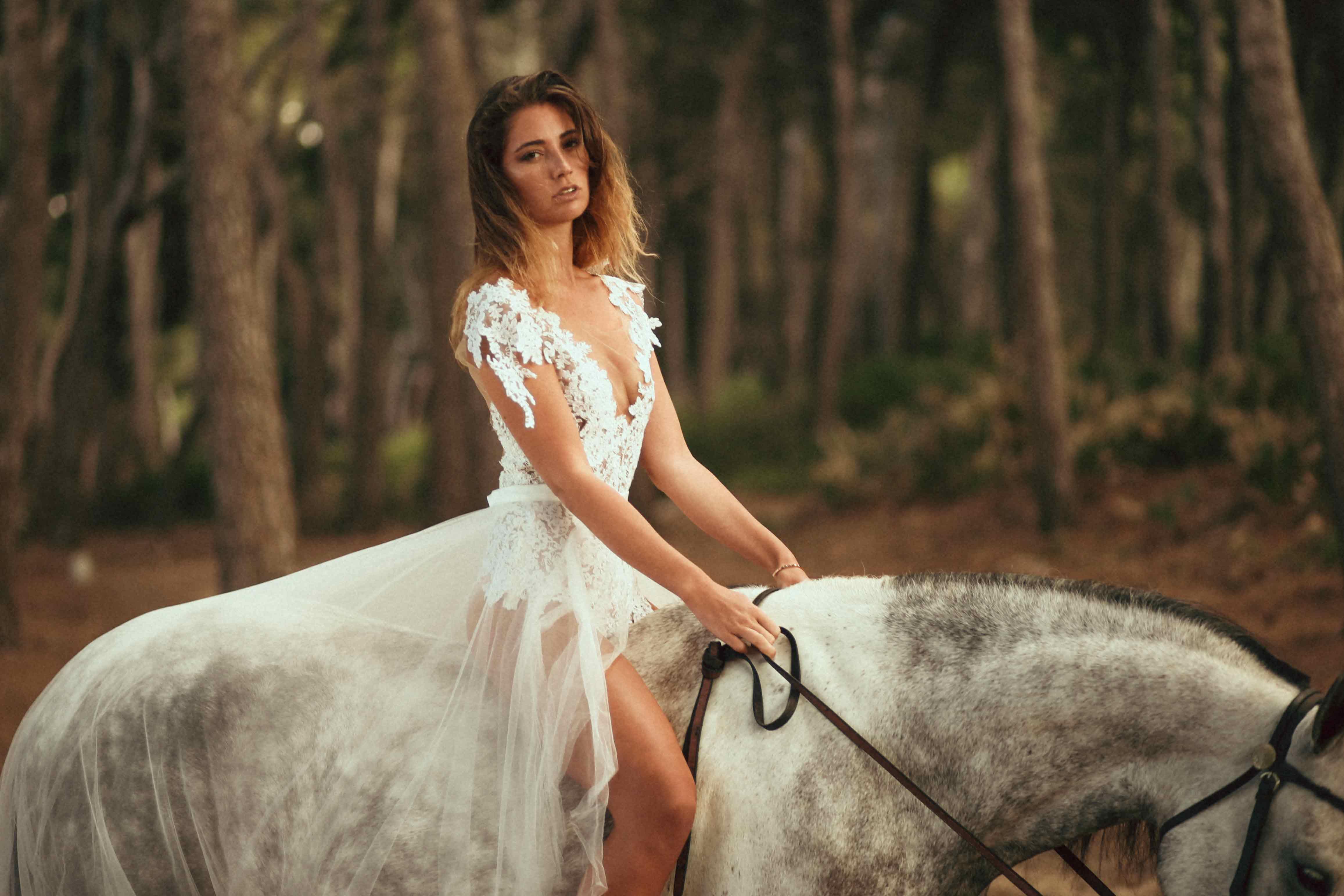 Eine blonde Frau trägt einen Spitzenbody und eine Schleppe als Brautkleid. Sie sitzt auf den Rücken eines Schimmels in einem spanischen Wald.