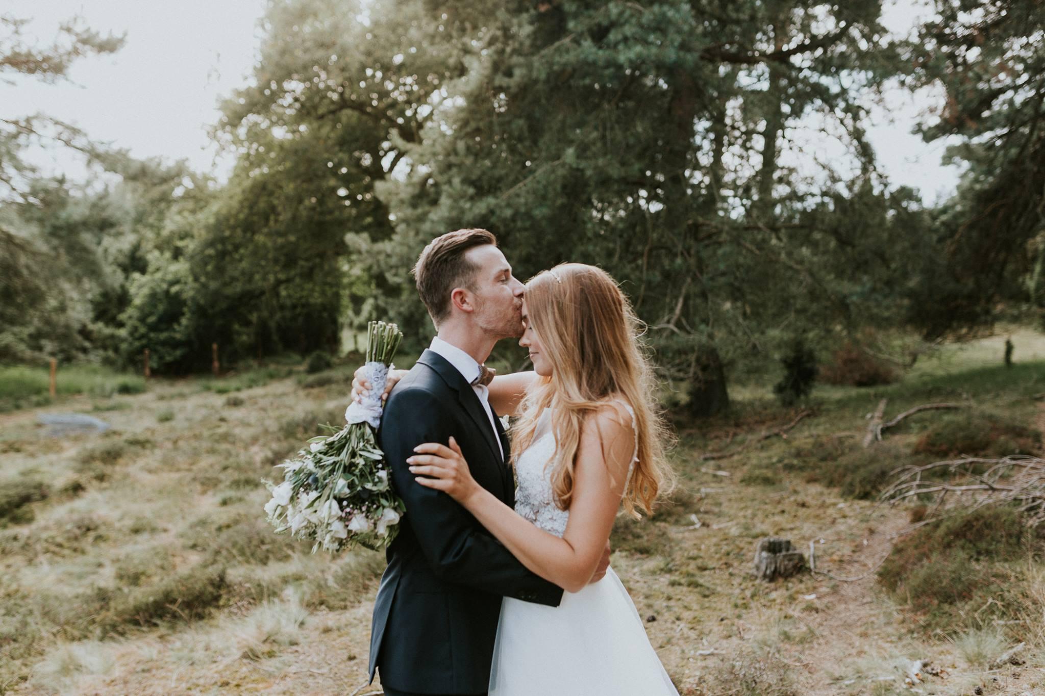 Der Bräutigam küsst seine Braut auf die Stirn. Die Braut trägt den Spitzenbody Lovely, die Schleppe Sully, sowie einen schmalen Haarreif in den offenen, langen Haaren.