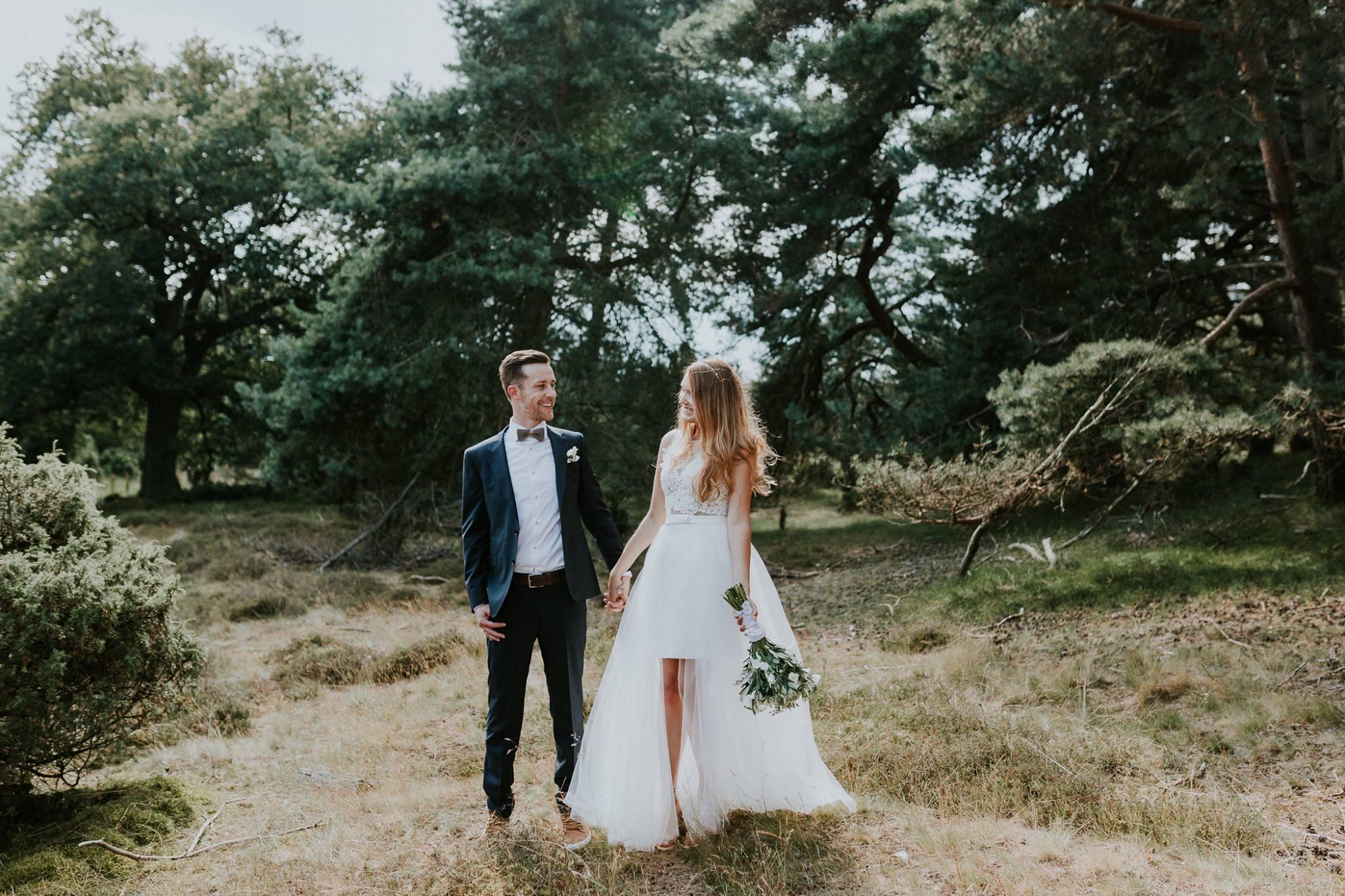 Das lächelnde Brautpaar steht in einem grünen Wald. Die Braut trägt einen Spitzenbody, einen weißen engen Rock, sowie eine zarte Schleppe. Die Haare fallen ihr sanft über die Schultern.