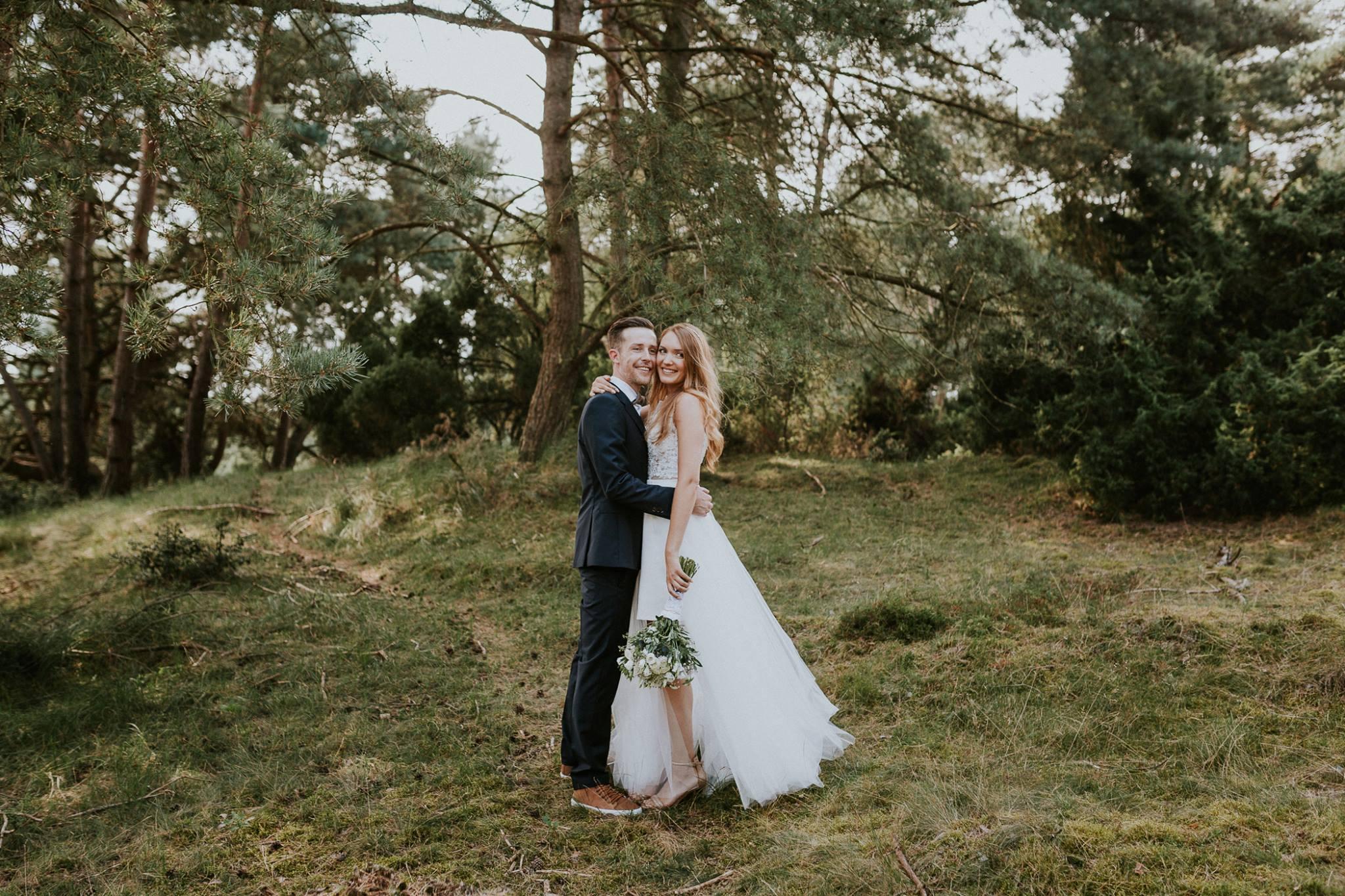 Das Brautpaar steht in einem grünen Wald. Die Braut trägt einen Spitzenbody, einen weißen engen Rock, sowie eine zarte Schleppe.