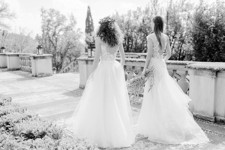 Zwei Bräute, die jeweils einen Spitzenbody tragen und weite, fließende Röcke. Das Foto ist schwarz weiß und zeigt eine Villa in der Toskana.