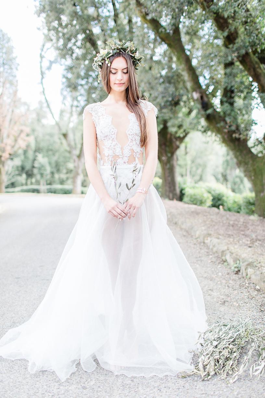 Die Braut trägt einen Body aus feiner Spitze und einen lange zarten Rock. Sie steht barfuß auf einer Straße in der Toskana und hält einen Olivenzweig in den Händen.