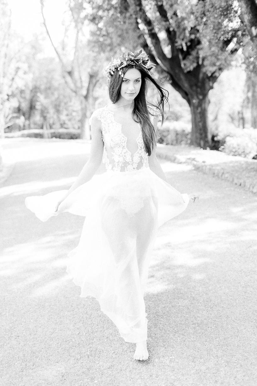 Ein Foto einer Braut in schwarz weiß. Das Model trägt einen Body aus feiner Spitze und einen zarten Rock. Sie hat lange glatte Haare und trägt einen Kranz aus Olivenzweigen.