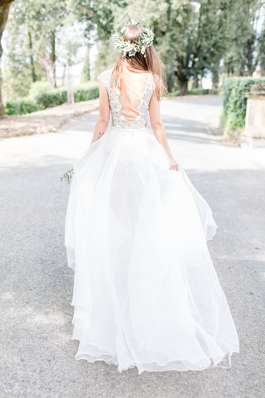 Eine bezaubernde Braut mit einem Kranz aus Olivenzweigen geschmückt, an einem schönen Sommertag in der Toskana. Sie trägt einen Body aus feinster Spitze und einen femininen Rock aus Tüll.