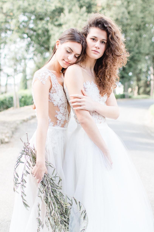 Zwei verträumte Bräute, welche die Bodys Sparkle und Hotzes LZ , sowie den verspielten Tüllrock Tully tragen. Sie stehen auf einem Weg in der Toskana an einem schönen Sommertag.