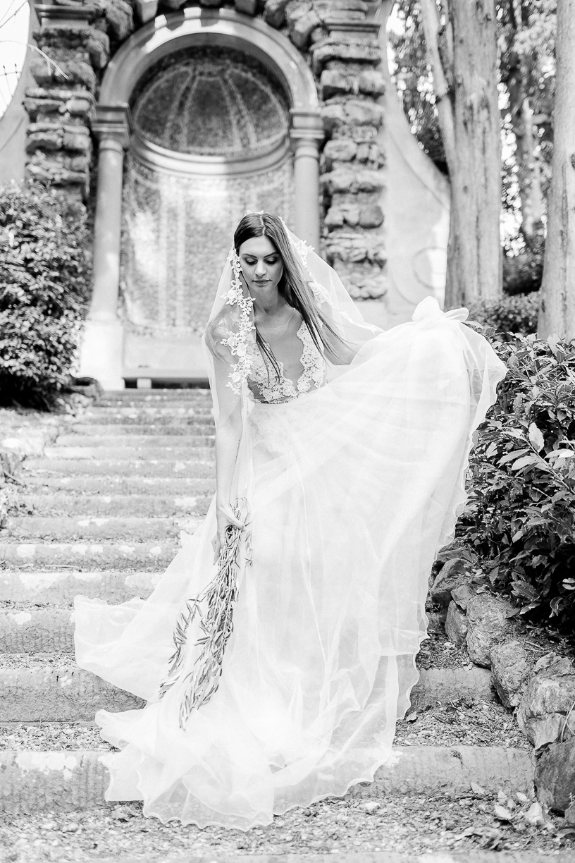 Die Braut trägt einen Schleier mit Spitze, einen transluzenten Rock, sowie den Spitzenbody Sparkle. Sie steht auf einer Treppe in der Toskana, vor einer Villa und bückt sich, um ihren Rock zu raffen.