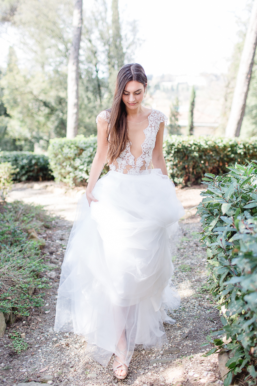 Die Braut trägt den Spitzenbody Sparkle, einen zarten Rock aus Tüll und Schuhe Jimmy Choo. Sie befindet sich in einem grünen Garten in der Toskana.