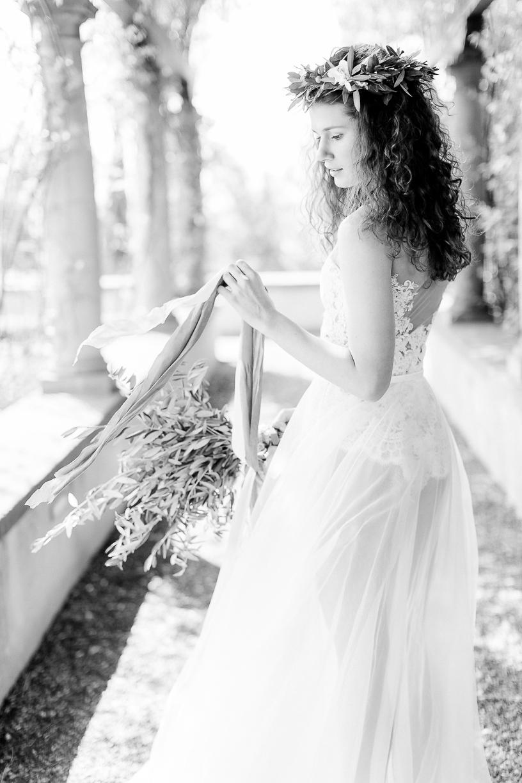 Das schwarz weiße Foto zeigt eine verträumte Braut, welche einen Spitzenbody mit einem tiefen Rückenausschnitt und einen zarten Rock aus Tüll trägt. Ihr lockiges Haar ist offen und sie trägt einen Olivenkranz in den Haaren.