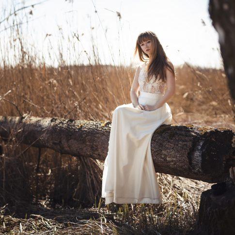 Model sitzt auf Baumstamm und schaut im Brautkleid aus Spitze in ivory verträumt in die Ferne.