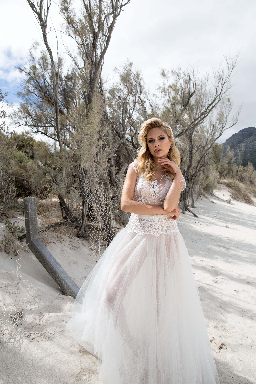 Blondes Model posiert im durchsichtigen Hochzeitskleid bestehend aus glitzerndem Top aus Spitze und Tüll-Rock