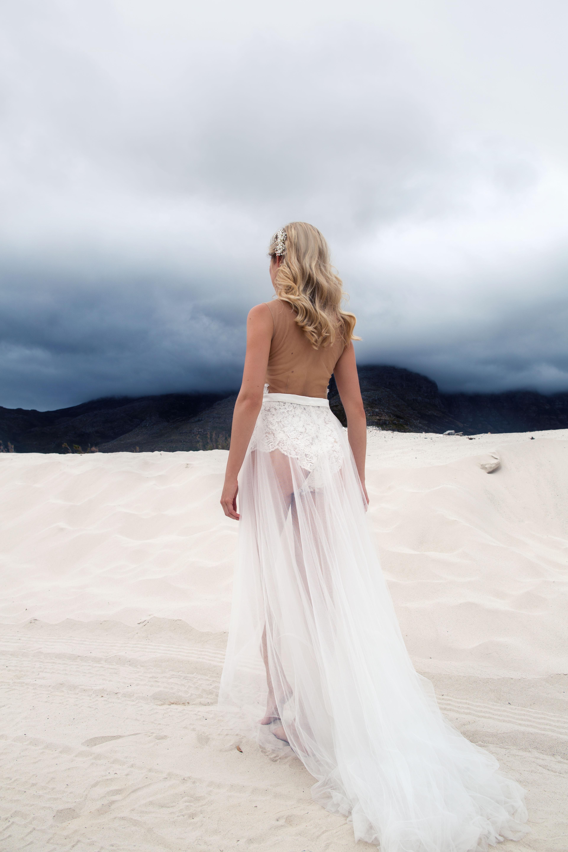 Rückansicht eines blonden Models im Brautkleid bestehend aus rückenfreiem Spitzenbody