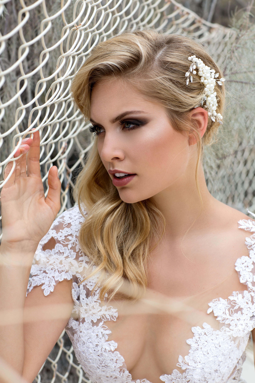 Nahaufnahme des blonden Models im Hochzeitskleid aus Spitze, am Zaun angelehnt in die Ferne schauend