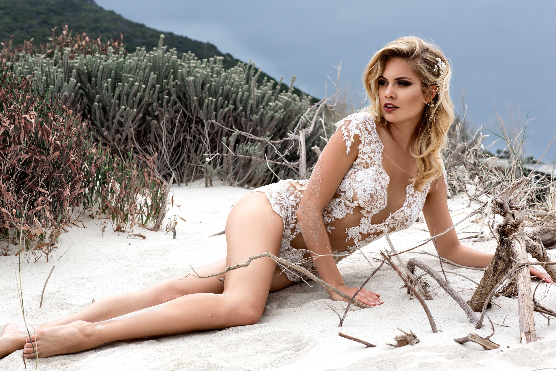 Model liegt am Strand und schaut verträumt in die Ferne - ein glitzernder Body als Hochzeitskleid