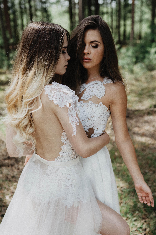Eine blonden eine brünette Frau stehen sich im Wald gegenüber, die blonde legt ihren Arm zärtlich um die Taille der Anderen. Beide tragen Spitzenbody, die Blonde mit einer Schleppe, die Brünette mit einem Brautkleid - Rock.