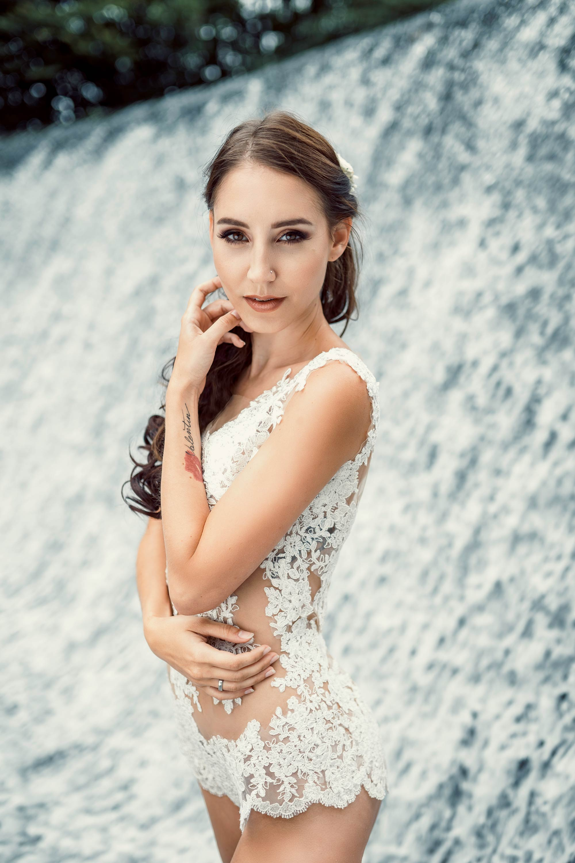 Eine brünette Frau steht seitlich verdreht mit dem Gesicht zu einem gewandt. Sie trägt einen Braut - Spitzenbody und steht vor einem Wasserfall.