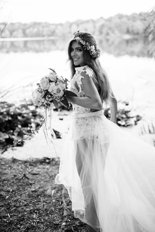 Eine brünette Frau steht mit dem Rücken zum Betrachter und schaut ihn über die linke Schulter hinweg an. Sie trägt einen Spitzenbody und eine Schleppe, aus ihrem haar sitzt ein Blumenkranz, in ihrer linken Hand hält sie einen Braut - Blumenstrauß.