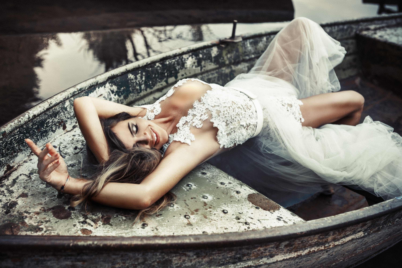 Eine brünetteFrau liegt auf dem Rücken und räkelt sich über die Sitzbänke eines alten Bootes. Sie trägt einen Spitzenbody und eine Schleppe.