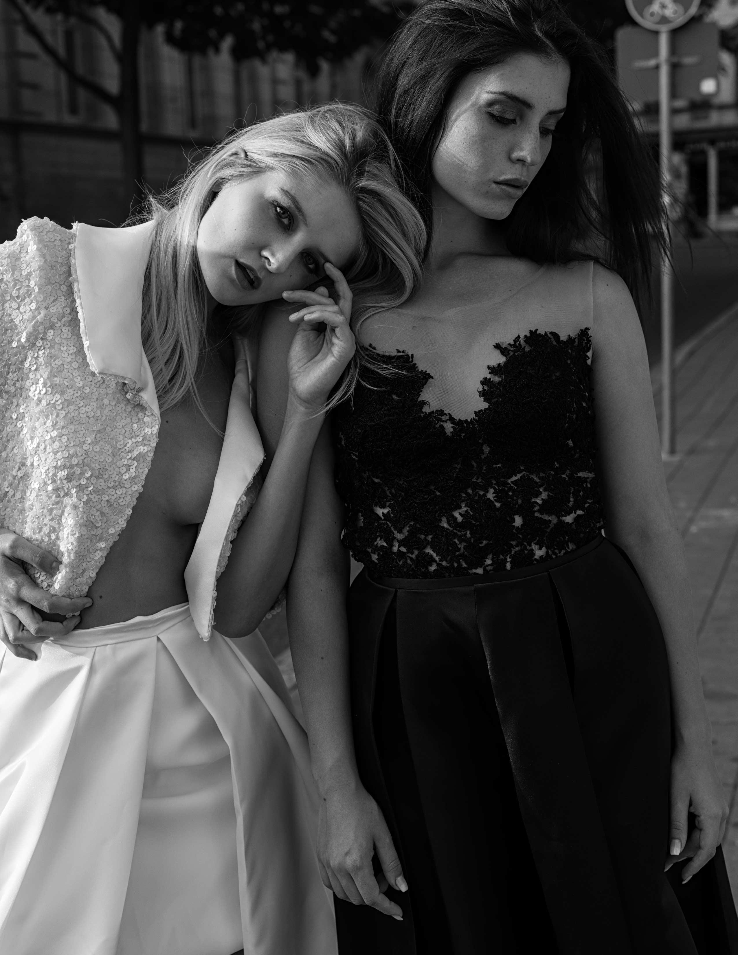 Links steht eine blonde, rechts eine brünette Frau. Die Blonde trägt ein weißes Brautoutfit, die Brünette einen schwarzen Zweiteiler.