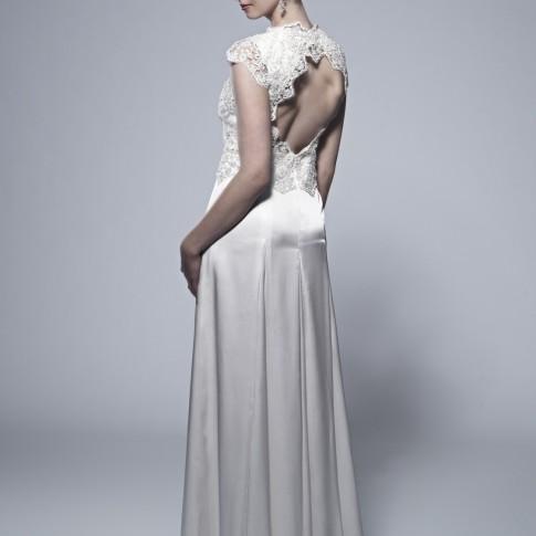 Im Bild zu sehen ist eine dunkelhaarige Frau die ein langes Kleid trägt. Ihre Haare sind in einer Hocksteckfrisur hochgebunden sie guckt nach rechts und hält mit ihrer rechten Hand leicht am Kleid fest.