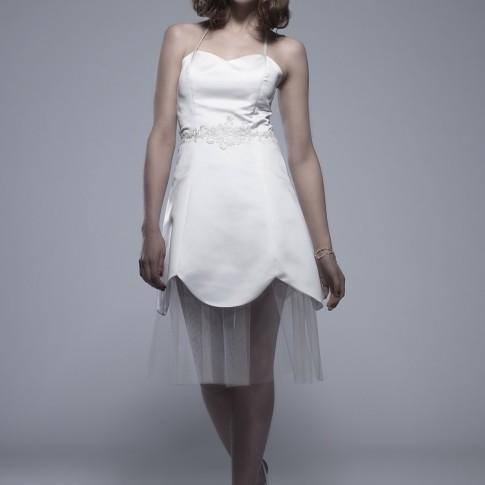 Im Bild zu sehen ist eine junge dunkelhaarige Frau mit kurzen Haaren. Sie trägt einen silbernen Kopfschmuck und ein kurzes weißes Kleid. Sie hat ein Bein vor das andere gelegt und steht gerade zum Betrachter.