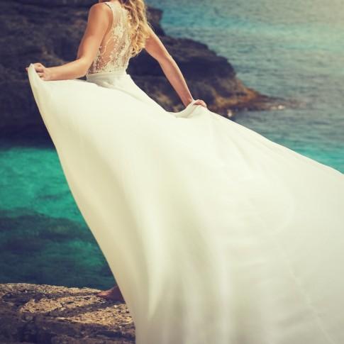Eine junge blonde Frau steht auf einem großen massigen Felsen mit dem Rücken zur Kamera. Sie trägt einen weißen Spitzenbody mit einer langen Schleppe. Sie hat ihren Oberkörper seitlich zum Betrachter gedreht und hält die Schleppe mit beiden Hände.