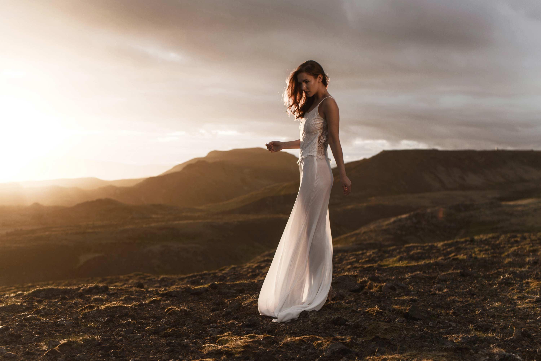 Brautkleid Sharon im Sonnenuntergang auf Island. Elfenbein weiße Spitze und leicher Chiffon. Handgemachtes Designer Hochzeitskleid aus Düsseldorf Deutschland. Goldener Himmel Iceland Sunset