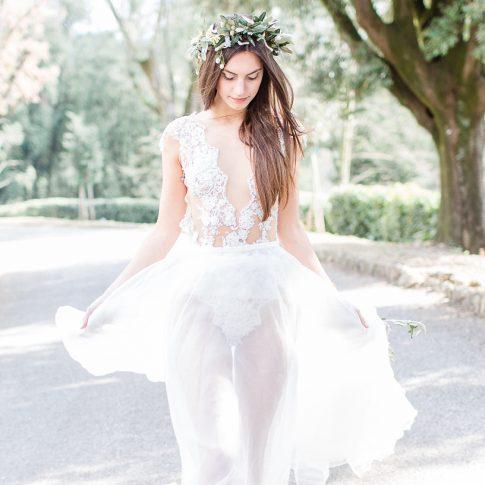 Das Model trägt einen Body aus feiner Spitze und einen zarten Rock. Sie hat lange glatte Haare und trägt einen Kranz aus Olivenzweigen.