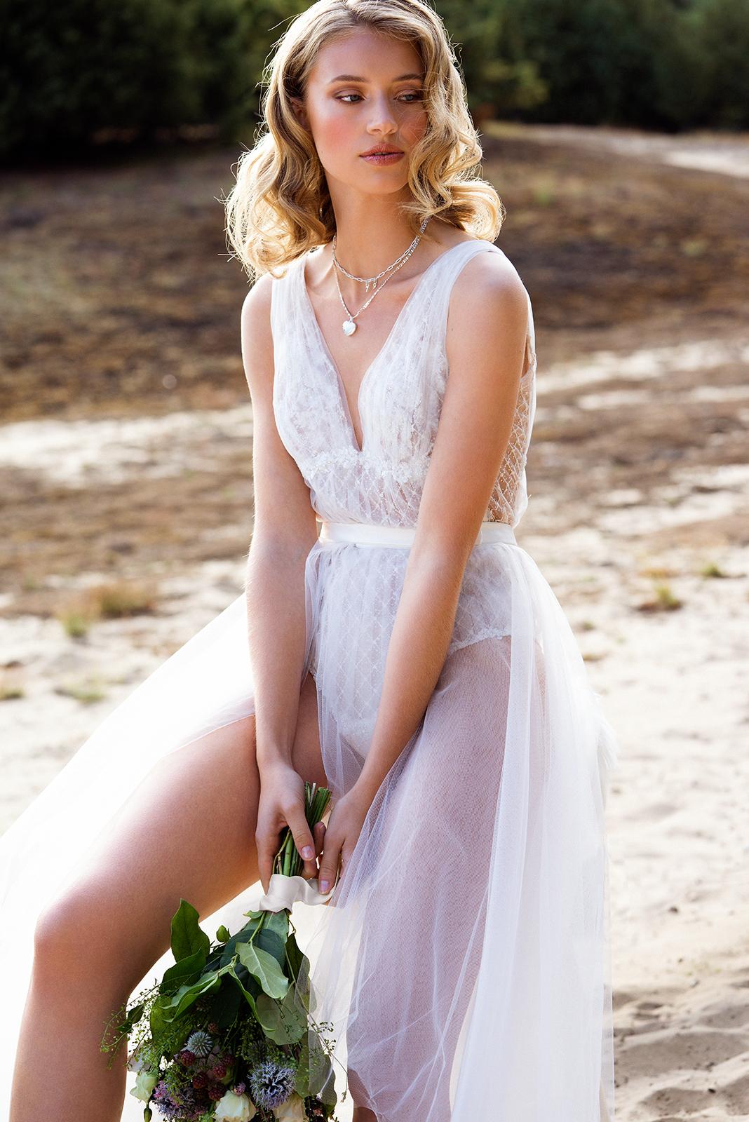 Blonde Frau trägt ein weißes Brautkleid bestehend aus Tüllrock und Tüllbody. Sie hält einen Blumenstrauß in der Hand.