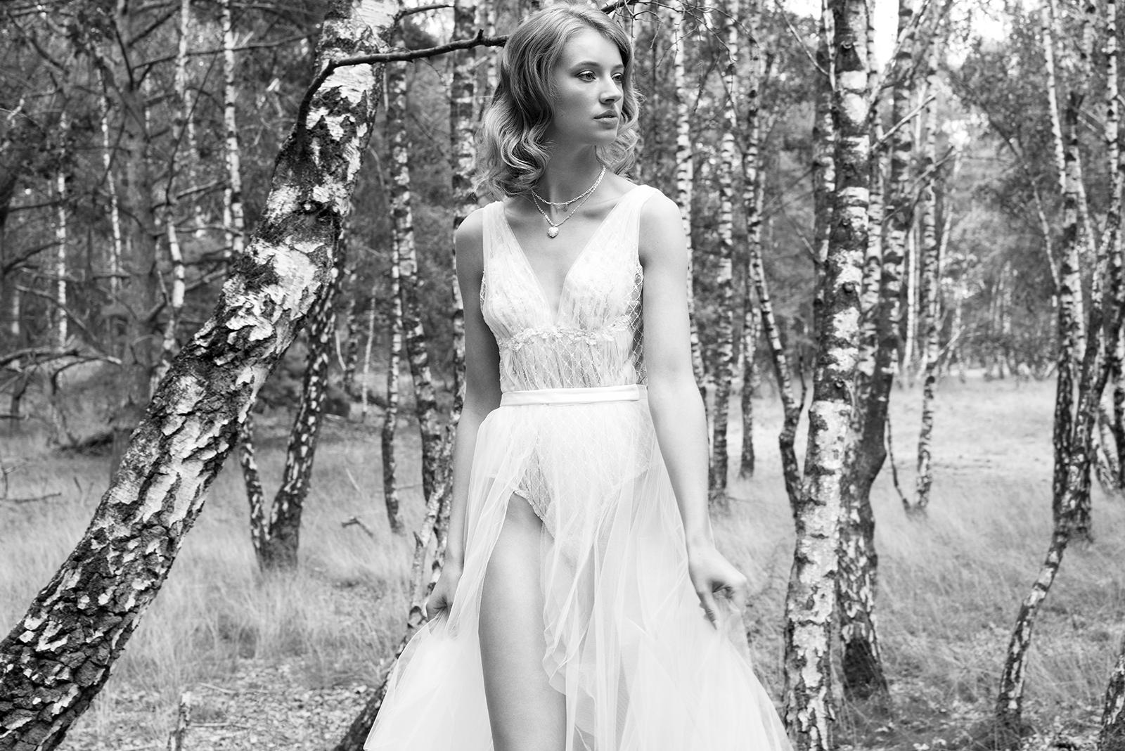 Blonde Frau trägt ein weißes Brautkleid bestehend aus Tüllrock und Tüllbody.