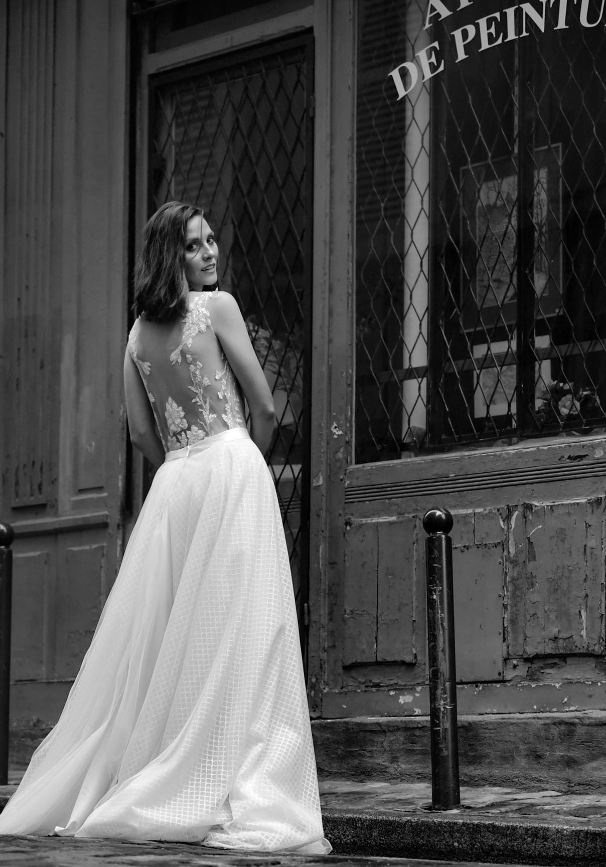 Eine brünette Frau trägt einen weißen Spitzenbody mit einem langen weißen Rock. Sie steht mit dem Rücken zum Betrachter und schaut über ihre Schulter nach hinten.