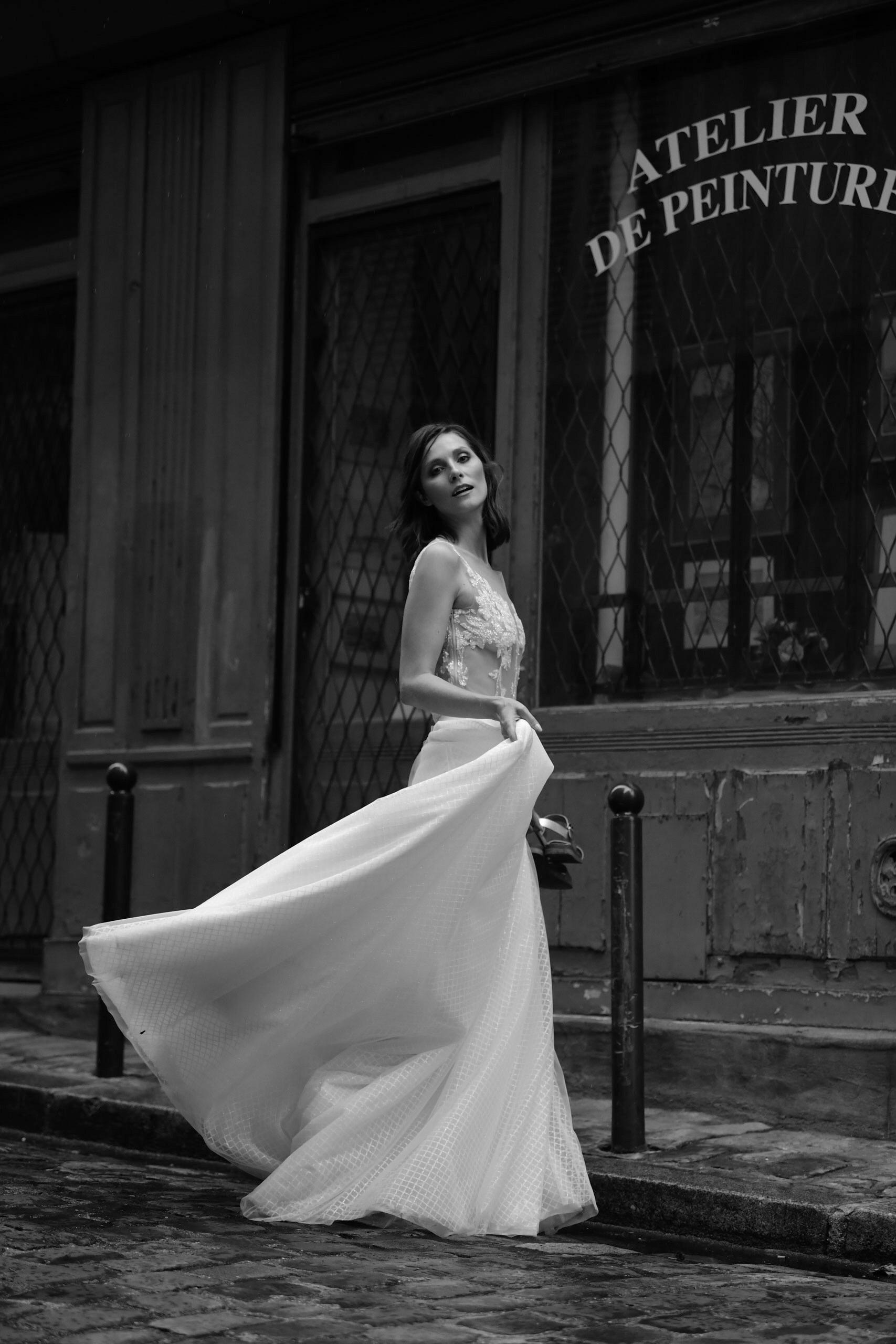 Eine brünette Frau trägt einen weißen Spitzenbody mit einem langen weißen Rock, während sie sich seitlich dreht.