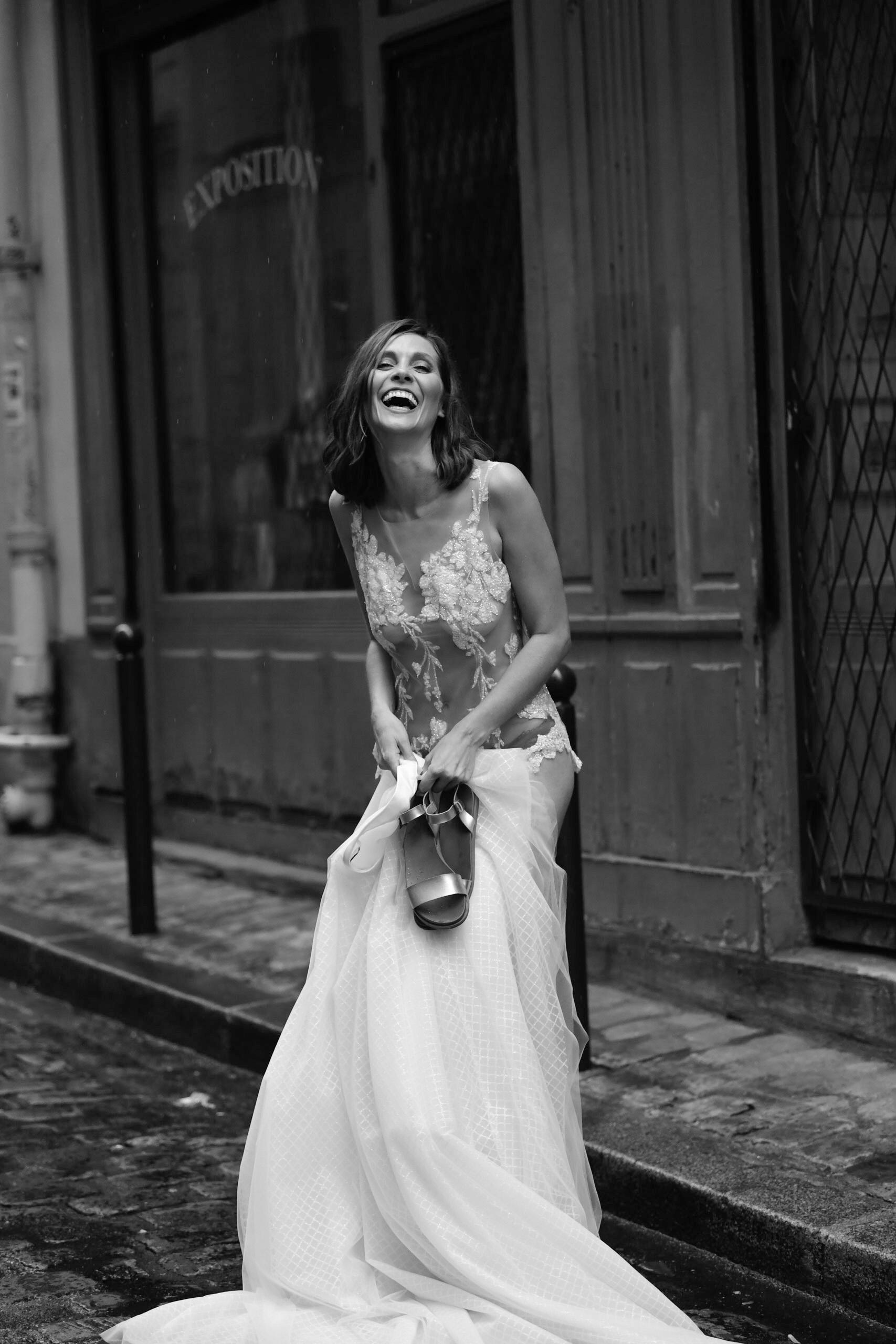 Eine lachende brünette Frau trägt einen weißen Spitzenbody mit einem langen weißen Rock.