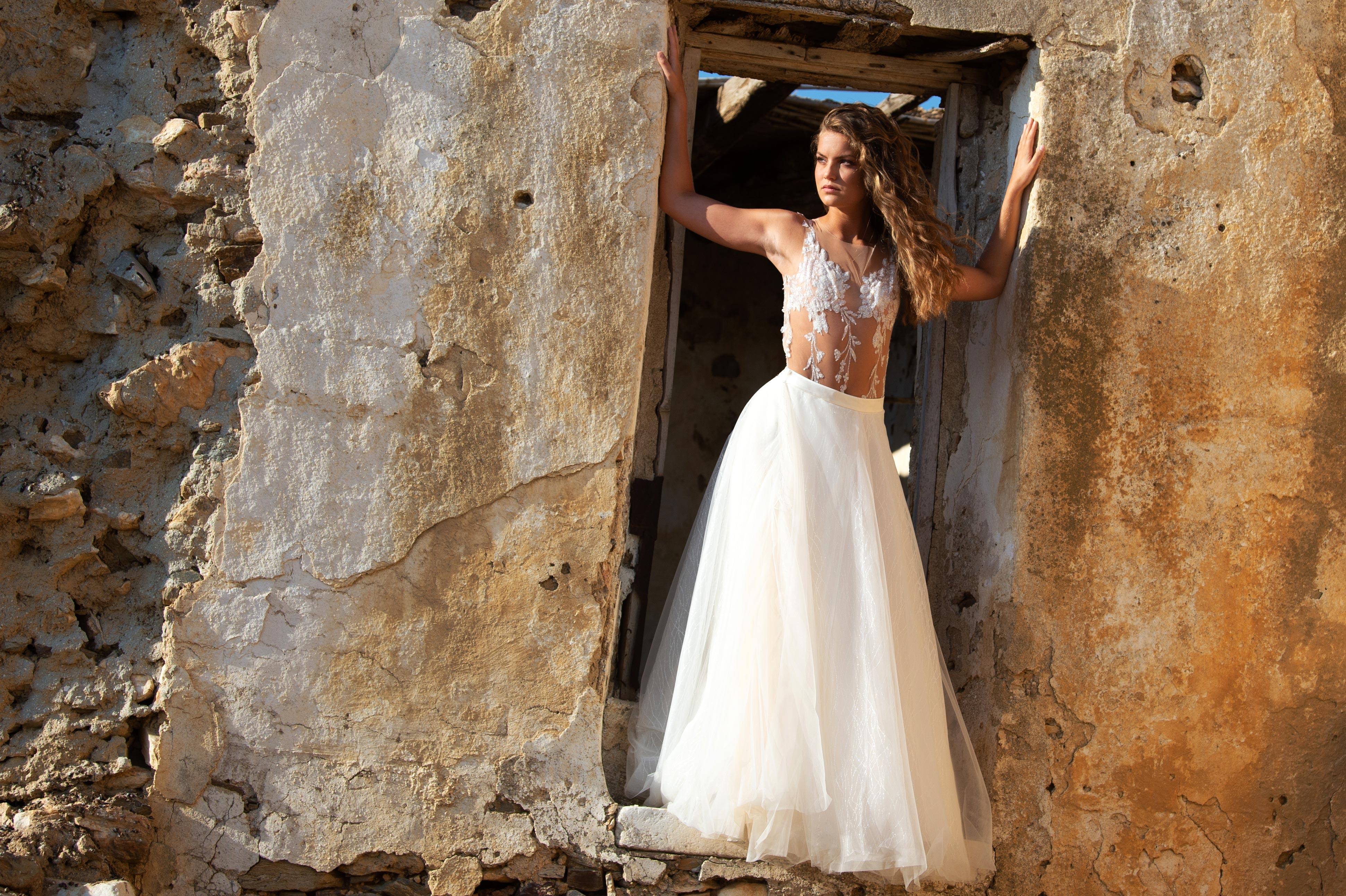 Brünette Frau trägt weißes langes Brautkleid und steht in einer Tür.