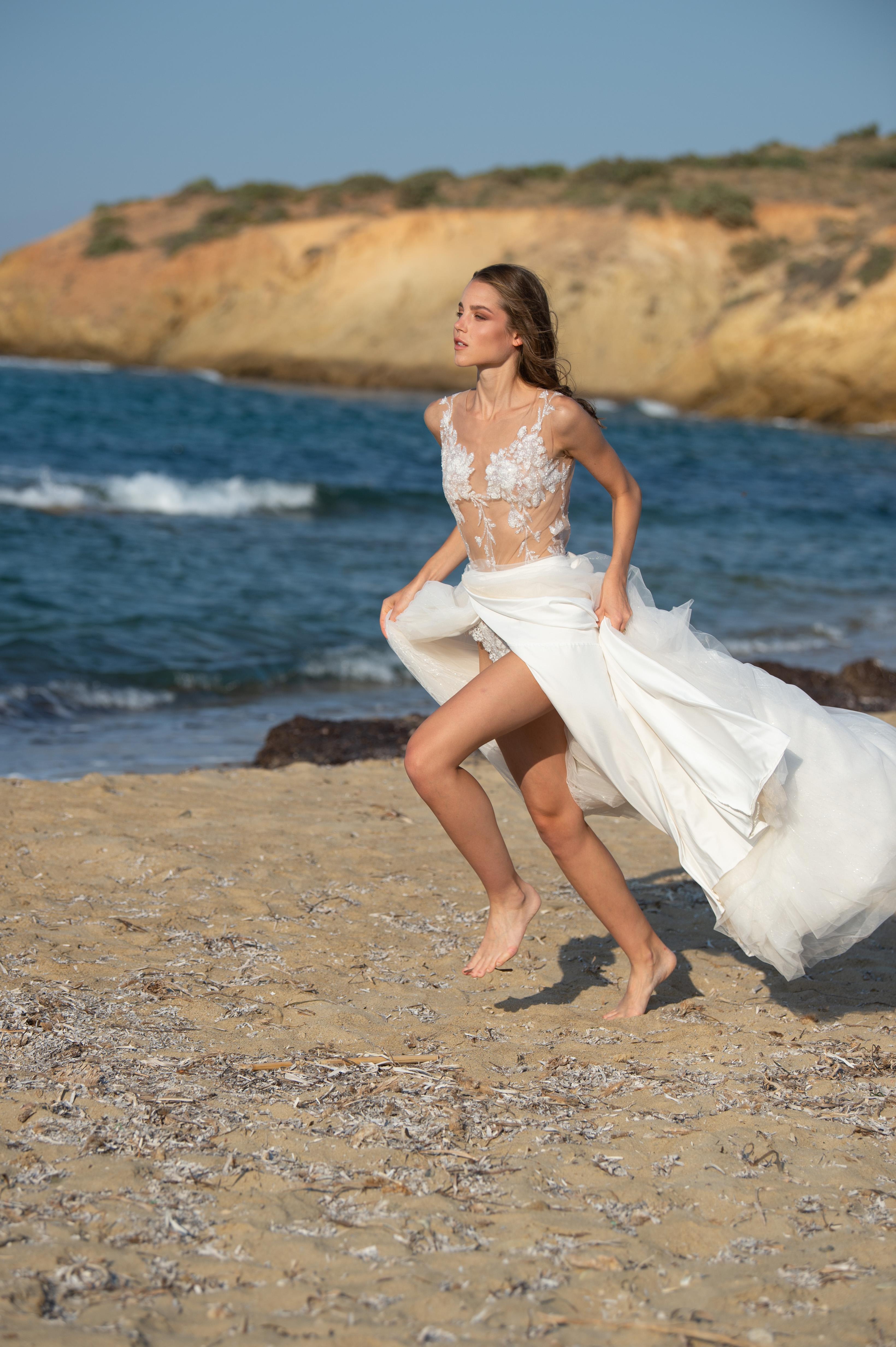 Frau in weißem Brautkleid läuft über den Strand am Meer.